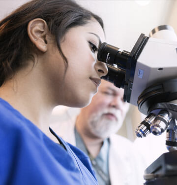 Nurse at microscope in medical clinic